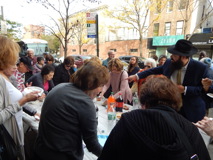 Rabbi Lubin encouraging people to taste the herring.